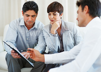 Buy stock photo Financial agent explaining details to couple with man holding the contract