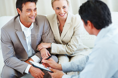 Buy stock photo Smiling couple discussing investment plans with financial advisor
