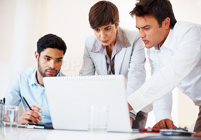 Buy stock photo Business team sitting at table and discussing project on laptop