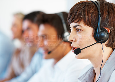 Buy stock photo Closeup of an attractive female operator looking away with colleagues in background
