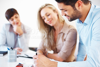 Buy stock photo Colleagues sitting at table and discussing during business meeting