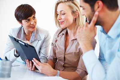 Buy stock photo Business partners going through clipboard during meeting and smiling