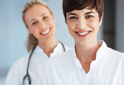 Buy stock photo Closeup of beautiful female doctor with colleagues in background