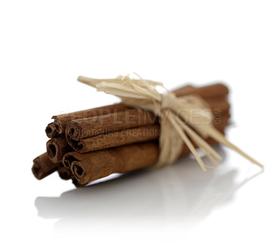 Buy stock photo Bunch of spicy cinnamon sticks tied by straw isolated on white background