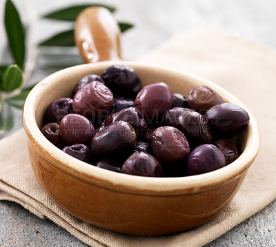 Buy stock photo Closeup of ceramic salad bowl full of dry black olives on a napkin at the table