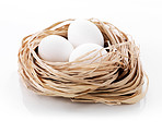Three chicken eggs in a nest on white