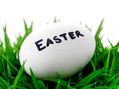 Buy stock photo Closeup image of Easter word written white egg on green grass bush