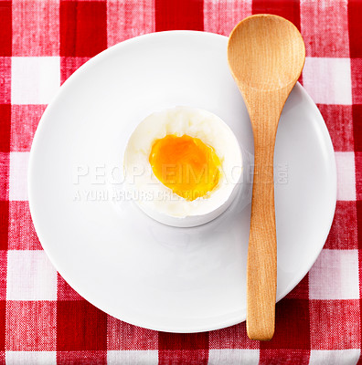 Buy stock photo Lightly boiled egg in porcelain eggcup with wooden spoon on dining table