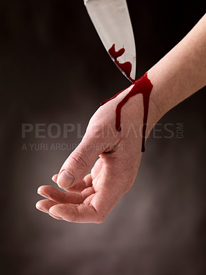 Buy stock photo Image of guy cutting veins with a sharp dagger attempting suicide against black background