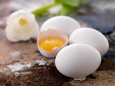 Buy stock photo Whole fresh raw eggs with a half broken egg on dirty floor