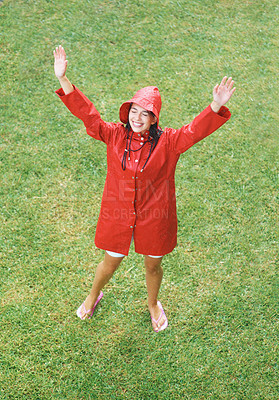 Buy stock photo Woman raising arms up while wearing raincoat in rain
