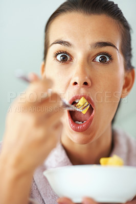 Buy stock photo Pretty woman making silly face as she eats fruit
