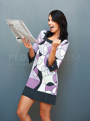 Buy stock photo Woman excited about something she read in the newspaper