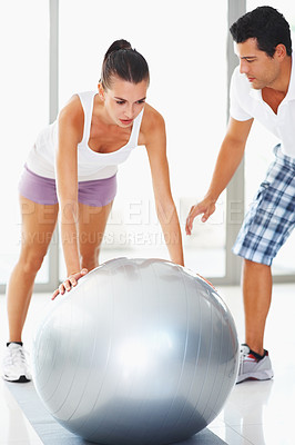 Buy stock photo Woman doing push ups on exercise ball assisted by personal trainer