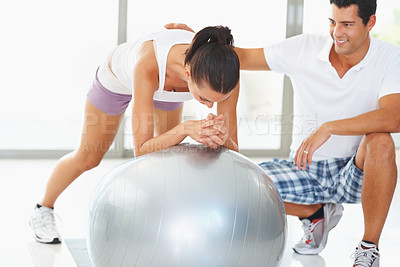 Buy stock photo Woman working on balance ball with fitness trainer