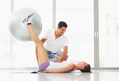 Buy stock photo Active woman exercising with fitness ball while trainer looking at her