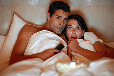 Buy stock photo Portrait of young couple watching scary movie while lying on the bed