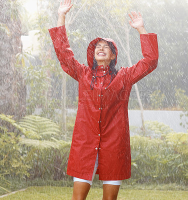Buy stock photo Portrait of young female in red raincoat with her hands raised in the rain