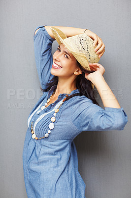 Buy stock photo Portrait of smiling young woman holding her hat against wall