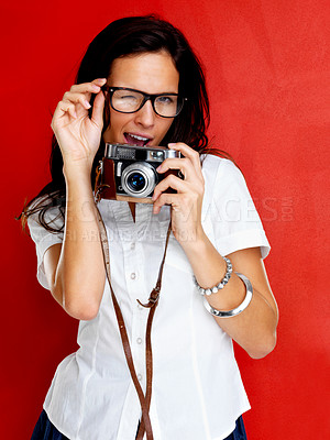 Buy stock photo Portrait of beautiful young woman in glasses holding a camera winking against red background