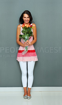 Buy stock photo Full length of attractive young woman holding bunch of fresh flowers