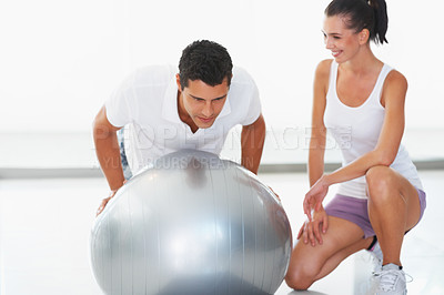Buy stock photo Trainer working on exercise ball while woman looking at him