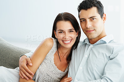 Buy stock photo Portrait of young couple sitting together and smiling
