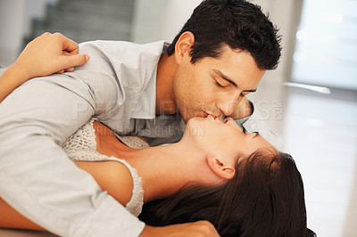 Buy stock photo Portrait of young couple having affectionate kiss at home