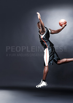 Buy stock photo Portrait of a young afroamerican guy in action with basketball on dark background
