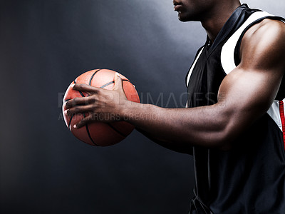Buy stock photo Cropped image of a young man playing basketball against grunge background
