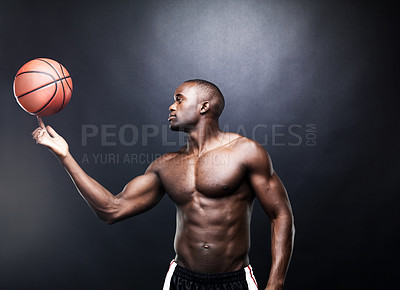 Buy stock photo Portrait of a healthy African American guy spinning a basketball on his finger on a dark background