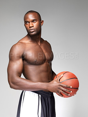 Buy stock photo Portrait of a handsome young black guy holding a basketball and looking away against white background
