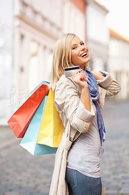 Buy stock photo Young pretty female smiling at you while standing in a street and holding a credit card and shopping bags - copyspace