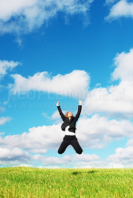 Buy stock photo Portrait of young business woman leaping over green grass against blue sky