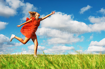 Buy stock photo Portrait of young woman in red dress running over green grass