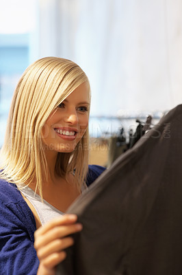 Buy stock photo Pretty young woman looking at the clothes in store