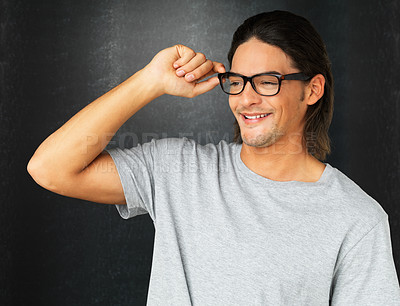 Buy stock photo Handsome man adjusting glasses while smiling against gray background