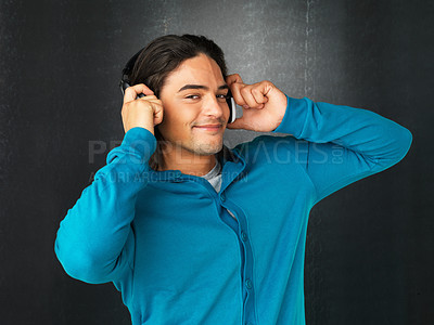 Buy stock photo Man listening to headphones against gray background