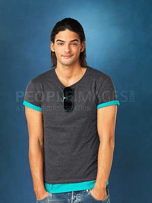 Buy stock photo Casual man standing with hands in pockets against blue background