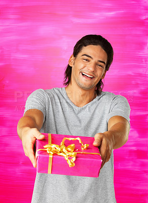 Buy stock photo Handsome man presenting gift while smiling against pink background