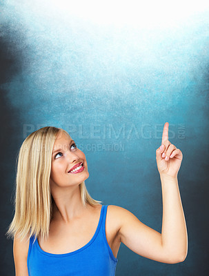 Buy stock photo Beautiful woman smiling while pointing up at copyspace