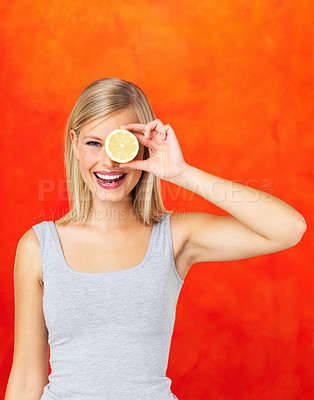 Buy stock photo Woman holding up lemon up to her eye on orange background