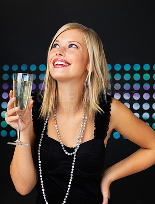 Buy stock photo Smiling woman holding wine glass and looking up