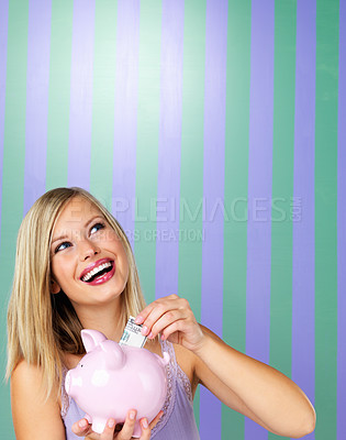 Buy stock photo Beautiful woman holding piggybank with money and looking up at copyspace