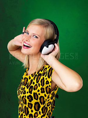 Buy stock photo Beautiful young woman looking at you while listening to music
