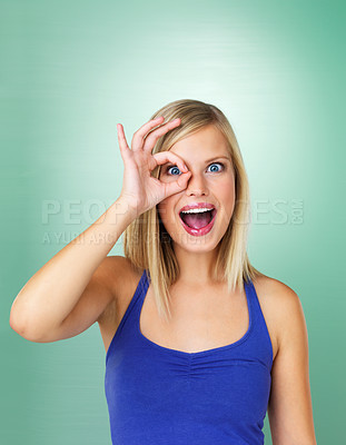 Buy stock photo Surprised young woman shows loophole on green background