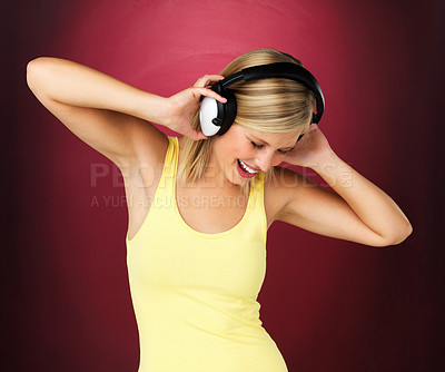 Buy stock photo Blonde woman listening and dancing to music in a yellow top against a maroon background