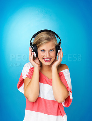 Buy stock photo Pretty woman wearing headphones against blue background