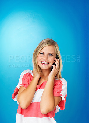 Buy stock photo Pretty woman smiling while on cell phone against blue background
