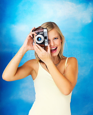 Buy stock photo Happy woman taking photo with vintage camera against a bright sky backdrop